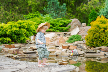 Cute child fishing by the pond in the beautiful garden
