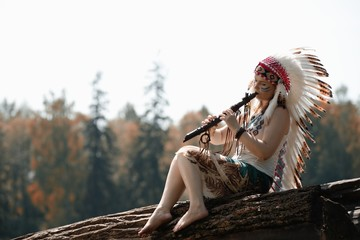 Girl in war bonnet of American Indian plays on tree a flute