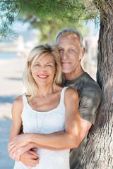attraktives älteres paar lehnt an baumstamm