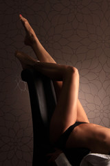 Beine einer Frau auf Stuhllehne