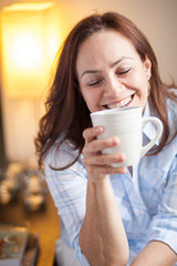 latin woman drinking from a mug - stock image