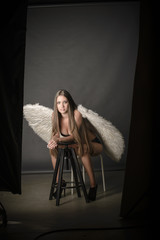 lingerie model posing in studio with angel wings