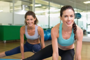 Fit women stretching on exercise mats