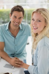 Hip young couple sitting at table smiling at camera