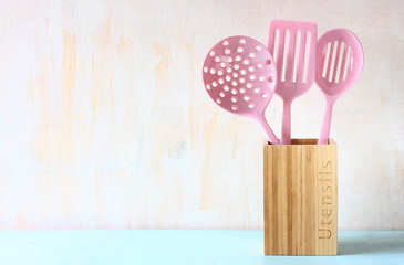 kitchen utensils over wooden textured background