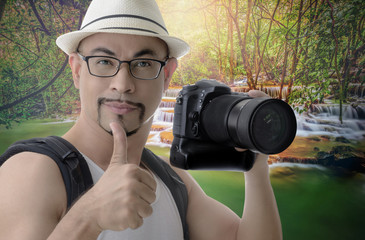 man traveler smart muscle photographer on waterfall background