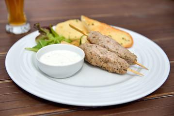 Kebab and beer with grilled vegetables, baguette and yogurt dip