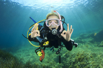 Spoed Fotobehang Duiken Young woman scuba diving signals okay