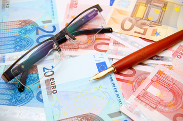 Pen and glasses for euro banknotes.