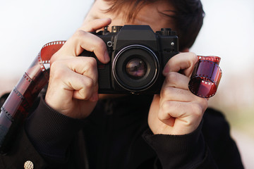 Young man photographer  holding vintage camera. outdoor
