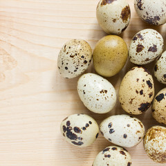 quail eggs over wooden background - top view