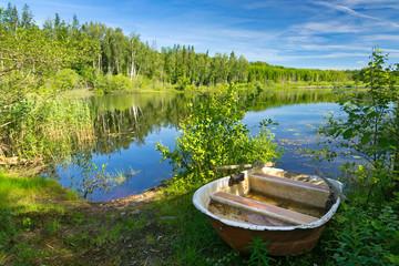 Small boat on a summer lake coast