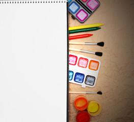 Notebook, school accessories on rumpled paper.