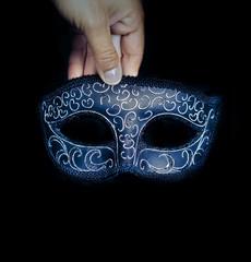 Hand holding Venetian mask