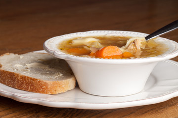 Bowl of chicken tortellini soup with a slice of sour dough bread on an antique plate