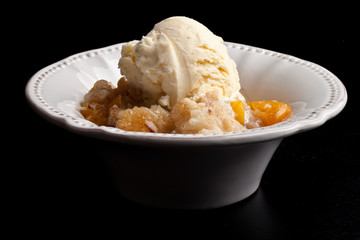 Homemade peach cobbler crisp in an antique white vintage bowl topped with vanilla ice cream isolated on a black background