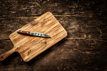 Empty chopping board on a distressed wooden table
