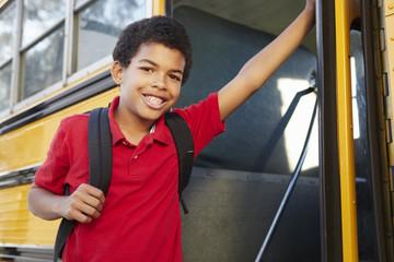 Pre teen boy getting on school bus