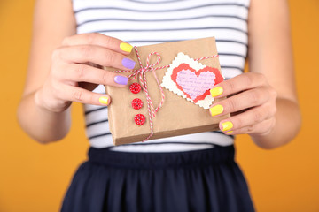 Woman with stylish colorful nails holding gift box, close-up,