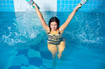 Attractive girl trains in aqua aerobics