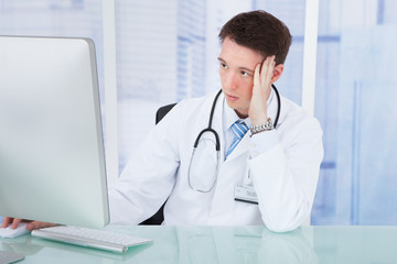 Worried Male Doctor Using Computer At Desk