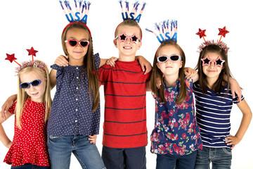 Five patriotic children standing arm in arm smiling