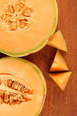 cut melon on wooden background close-up