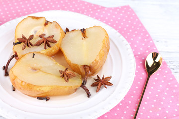 Baked pears with syrup on plate, on color wooden background