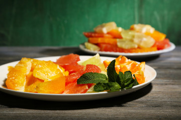 Sliced citrus fruits on plate, on wooden background