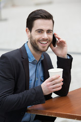 Young man smiling with phone and coffee