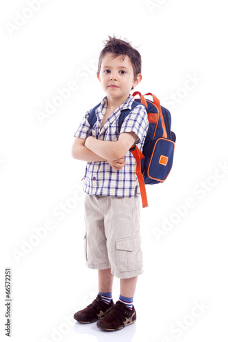 """Smiling school kid standing with arms crossed against ..."