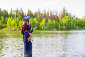 Young father and little adorable girl fishing on the river