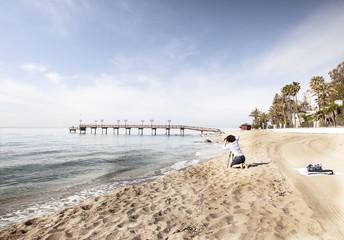 Joven mujer haciendo fotos en la playa