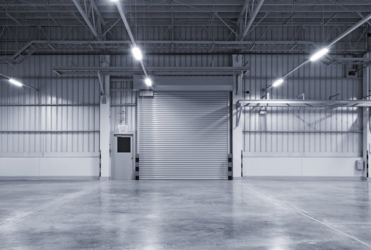 Roller door or roller shutter inside factory, warehouse or industrial building. Modern interior design with polished concrete floor and empty space for product display or industry background.
