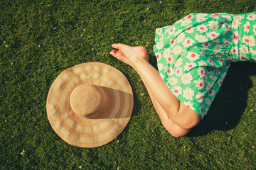 Young woman with hat sleeping in the park
