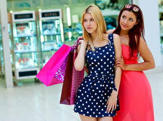 two woman friends in shopping mall with bags