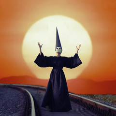 Wizard in black cloak and dunce hat standing on rails at sunset
