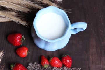 Ripe sweet strawberries, fresh bun and mug with milk