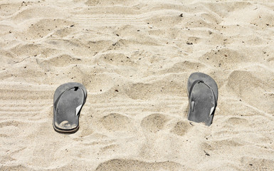 Pair of black sandals in sand.Relaxing on beach concept.