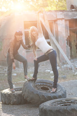 Brunette and blonde posing standing on giant tires outdoors