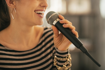 Closeup on happy young woman singing with microphone Fotobehang