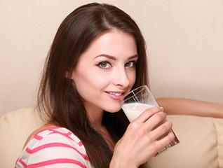 Smiling girl drinking yogurt or milk and hapy looking