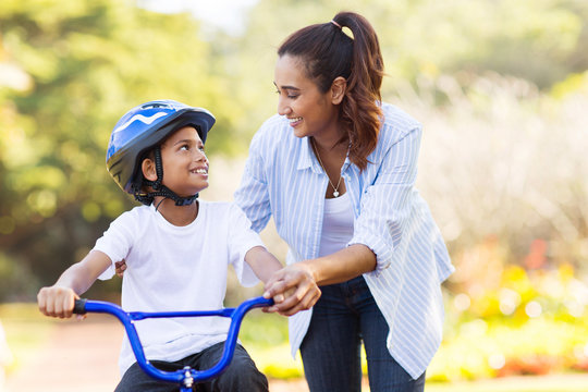 mother help her son ride a bicycle
