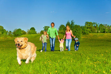 family walks with running dog in park