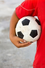boy with red t-shirt holding dirty black white football or socce