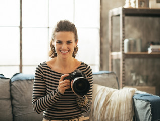 Portrait of happy young woman with modern dslr photo camera