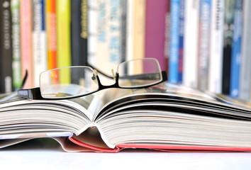 Offenes Buch mit Bücherreihe im Hintergrund