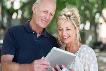 aktives seniorenpaar schaut auf tablet-pc