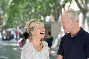 lachende ältere frau mit ihrem partner in der stadt