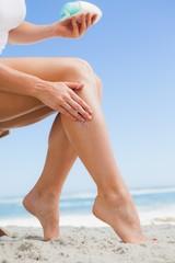 Woman rubbing sunblock on her leg at the beach